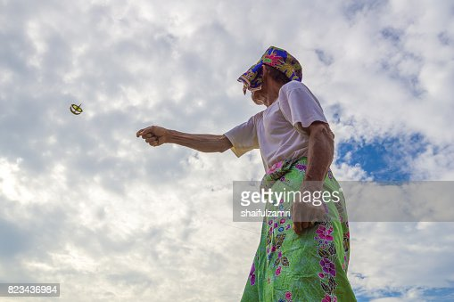 Unidentified man is playing the traditional moon kite or locally known as 'Wau Bulan' in Kelantan, Malaysia. : Stock Photo