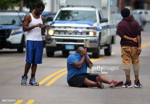 A unidentified man reacts in the middle of Hancock Street in the Dorchester neighborhood of Boston on July 7 where their was a double shooting that...