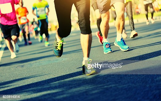 Unidentified marathon athletes legs running on city road : Stock Photo