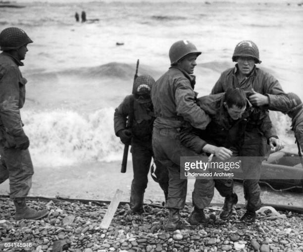Unidentified survivors from a sunken LCVP are helped ashore at Omaha Beach during the invasion of Normandy Normandy France June 6 1944