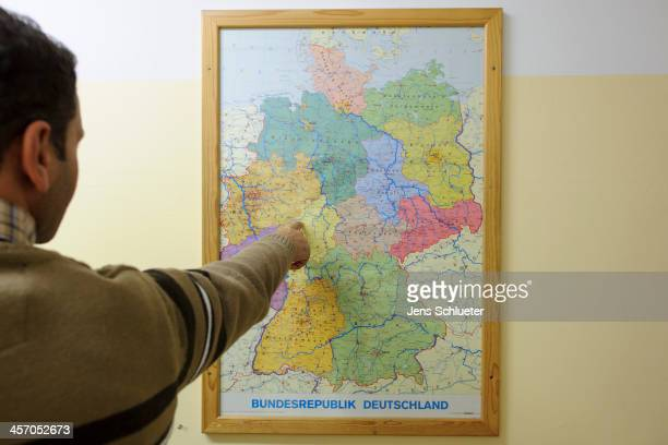 Unidentified Syrian refugee views a map of Germany at the refugee center on December 10 2013 in Friedland Germany Hundreds of thousands of Syrians...