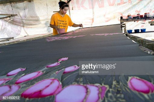 Unidentified woman use dye to make a 'Batik'. Making of Batik is part of Malaysia culture and tourist attraction in Kota Baharu, Kelantan. : Stock Photo