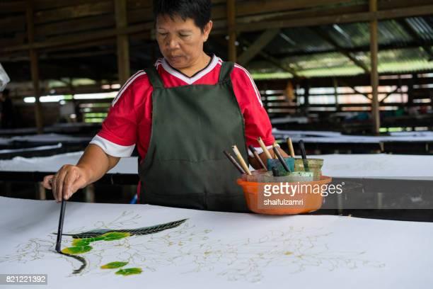 Unidentified woman use dye to make a 'Batik'