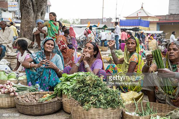 Unidentified women offer fresh vegetables for sale at a daily local market on March 27 2015 in Barkagaon Jharkhand Many of the people in this area...