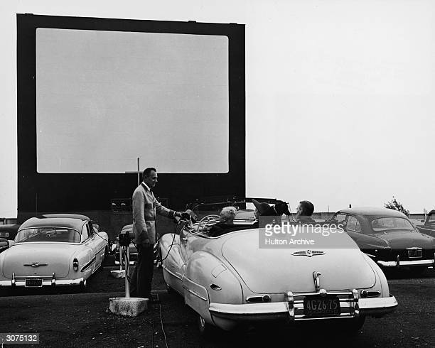 A uniformed drivein theater attendant hands a clipon speaker to the driver of convertible while the car's other passengers watch New York early 1950s