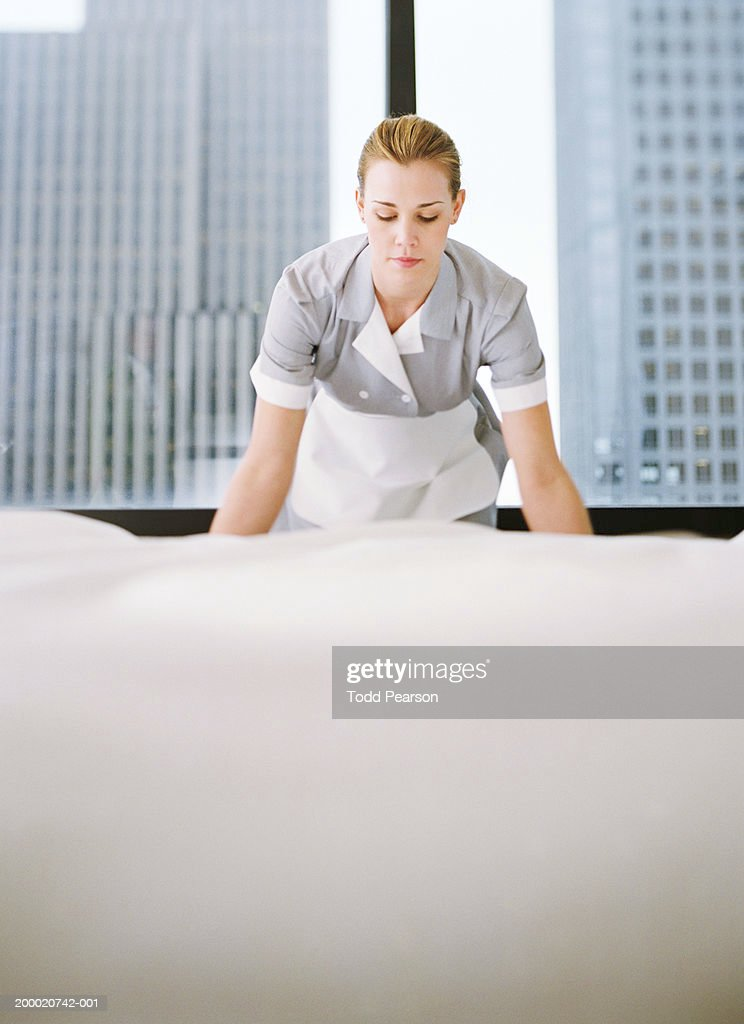 Uniformed hotel maid bent over making bed : Stock Photo
