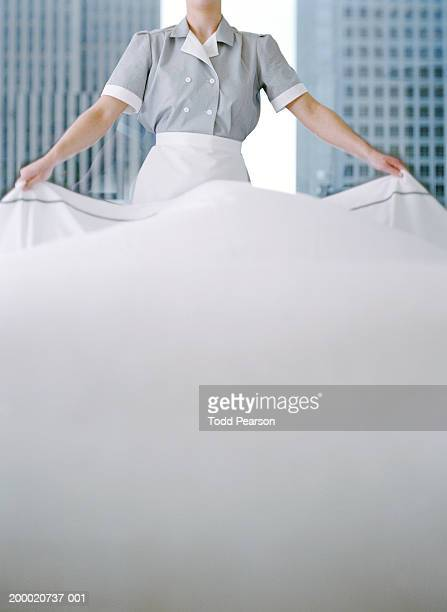 Uniformed hotel maid draping sheet over bed, mid section