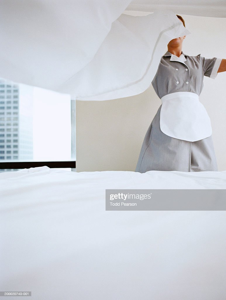 Uniformed hotel maid fanning sheet on bed