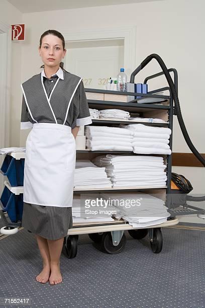 Uniformed maid standing next to push cart in hotel corridor