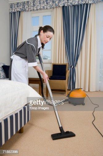 Uniformed Maid Using Vacuum Cleaner In Hotel Room Stock ...