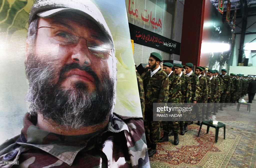 Uniformed militants form the Shiite Muslim Hezbollah movement file past the coffin and image of assassinated Hezbollah commander Imad Mughnieh in...