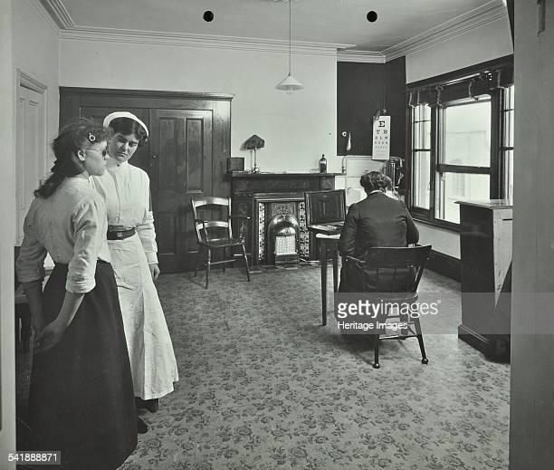 Uniformed nurse and optician Eye Room Fulham School Treatment Centre London 1914 A girl taking an eye examination Artist unknown