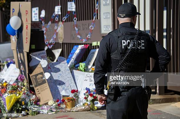 A uniformed Secret Service officer stands guard near a makeshift memorial outside the French Emabssy in Washington DC November 16 three days after a...