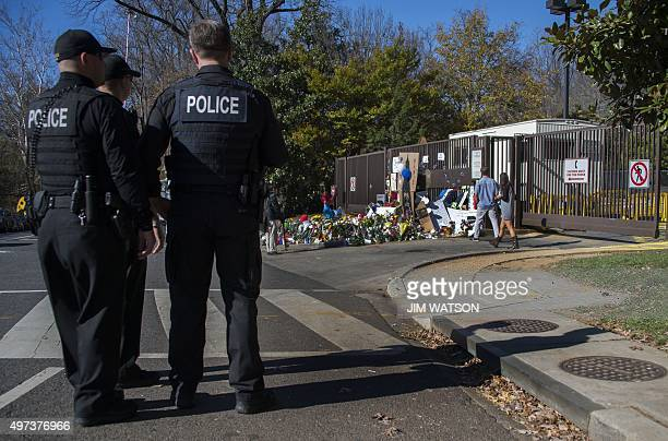 Uniformed Secret Service officers stand guard near a makeshift memorial outside the French Emabssy in Washington DC November 16 three days after a...