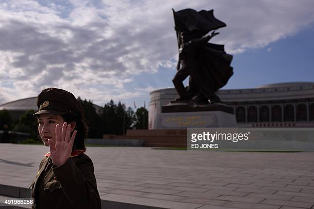 A uniformed tour guide gestures to tourists outside the War Museum in Pyongyang on October 9 2015 North Korea is gearing up for a lavish celebration...