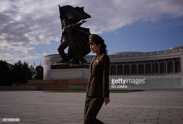 A uniformed tour guide walks before a statue outside the War Museum in Pyongyang on October 9 2015 North Korea is gearing up for a lavish celebration...