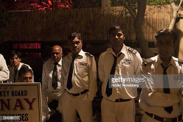 Uniformed valet drivers stand outside a Diwali party October 27 2011 waiting to retrieve cars of guests in New Delhi India