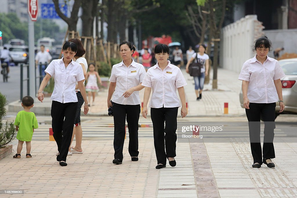 Uniformed workers walk down a street in Changsha, Hunan Province, China, on Friday, July 13, 2012. Gross domestic product (GDP) expanded 7.6 percent in the second quarter of 2012 from a year earlier, China's National Bureau of Statistics said today in Beijing. Photographer: Nelson Ching/Bloomberg via Getty Images