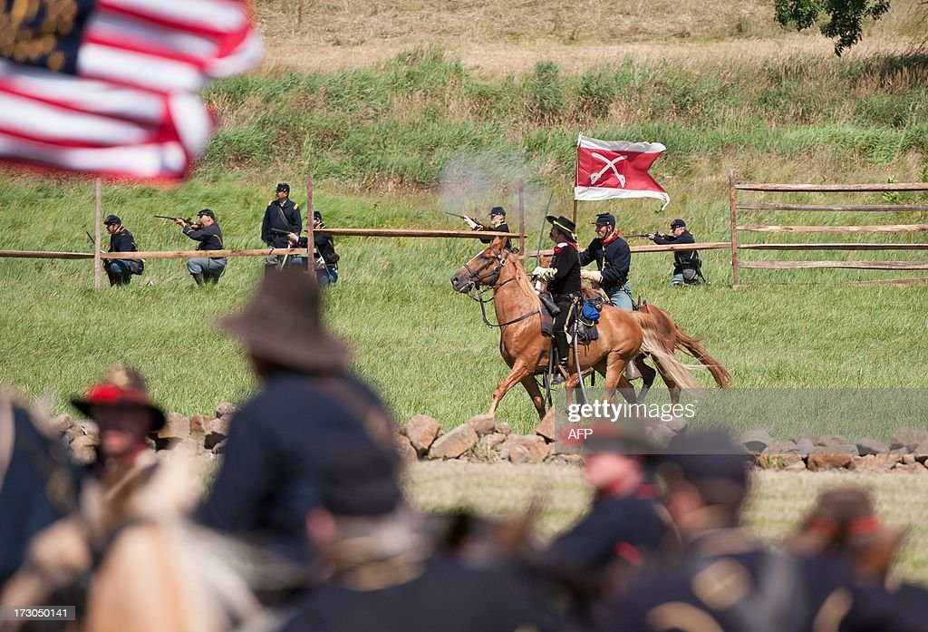 Union Brigadier General George Armstrong Custer (C) directs his troops while charging toward Confederate Cavalry, July 5, 2013 at the 150th Gettysburg celebration and re-enactments in Gettysburg, Pennsylvania. The Battle of Gettysburg is underway for the second time in a week and tourists turned out in droves even though the outcome of the Civil War's pivotal encounter has been known for 150 years. This re-enactment was held by the Gettysburg Anniversary Committee, the group which has held such events for roughly two decades. This event appeared to draw bigger crowds on the July 4th holiday than the re-enactments held last weekend by the Blue-Gray Alliance. AFP PHOTO / Karen BLEIER