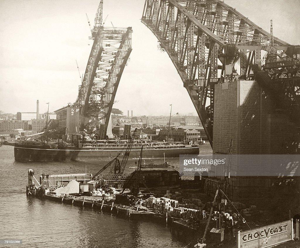A Union Castle Line ship passes beneath the Sydney Harbour Bridge still under construction between the Central Business District and the North Shore...