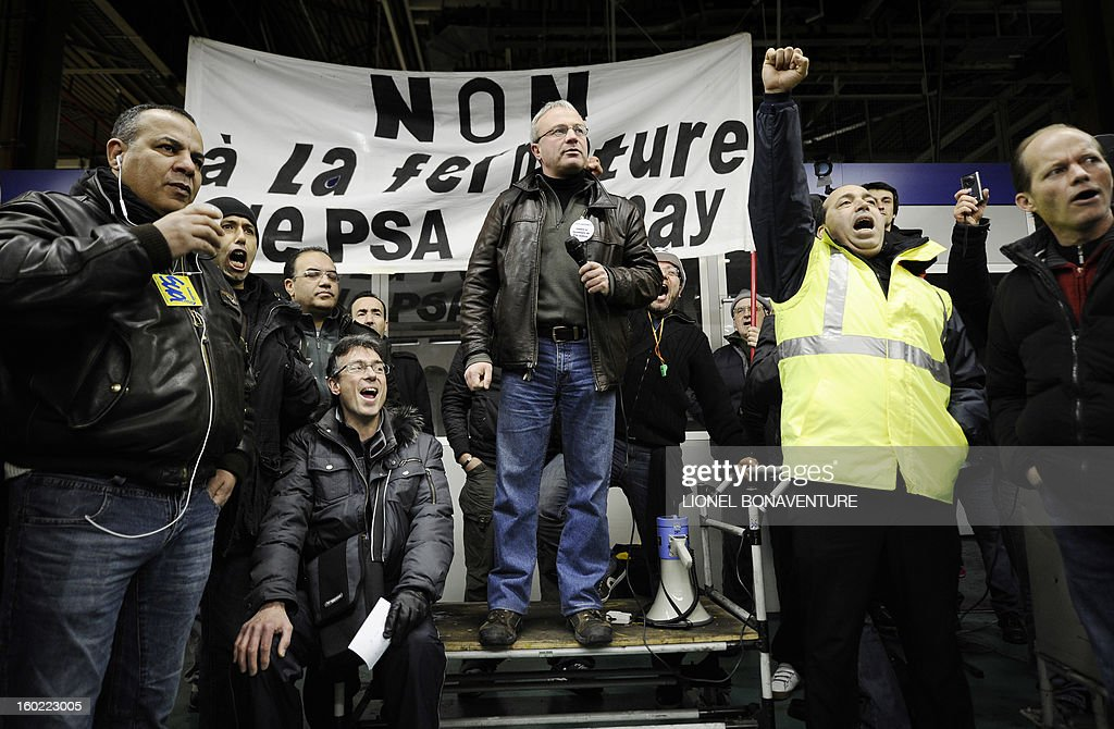 CGT union delegate Jean-Pierre Mercier delivers a speech as striking workers of the PSA Peugeot Citroen carmaker plant of Aulnay-sous-Bois, a Paris' suburb, take part in a general assembly, on January 28, 2013. The striking workers occupy the factory to protest against plans to sell the plant and lay off thousands of employees. AFP PHOTO LIONEL BONAVENTURE