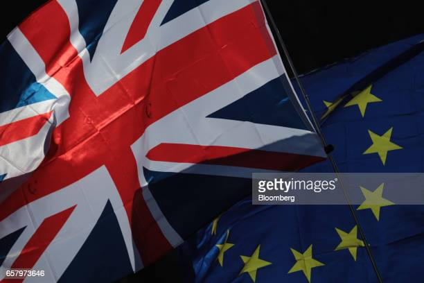 A Union flag also known as Union Jack left and a European Union flag fly during a Unite for Europe march to protest Brexit in central London UK on...