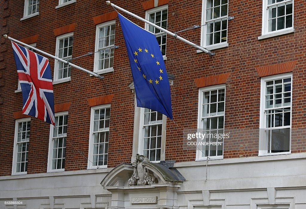A Union flag (L), and a European Union (EU) flag fly above Europe House, the head office of the UK Representation of the European Commission, and the UK Information Office of the European Parliament, which was formerly the building that housed the headquarters of the British Conservative Party, in central London on June 28, 2016. EU leaders attempted to rescue the European project and Prime Minister David Cameron sought to calm fears over Britain's vote to leave the bloc as ratings agencies downgraded the country. Britain has been pitched into uncertainty by the June 23 referendum result, with Cameron announcing his resignation, the economy facing a string of shocks and Scotland making a fresh threat to break away. / AFP / ODD