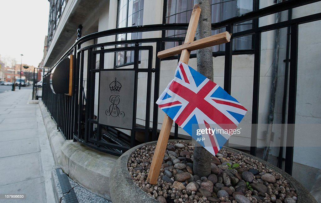 A Union Flag attached to a cross stands in a planter outside the King Edward VII hospital in central London on December 8, 2012 after nurse Jacintha Saldanha was found dead the previous day at a property close by. A nurse at the hospital which treated Prince William's pregnant wife Catherine, Duchess of Cambridge, was found dead on December 7, days after being duped by a hoax call from an Australian radio station, the hospital said. Police said they were treating the death, which happened at a property near the hospital, as unexplained. AFP PHOTO / WILL OLIVER