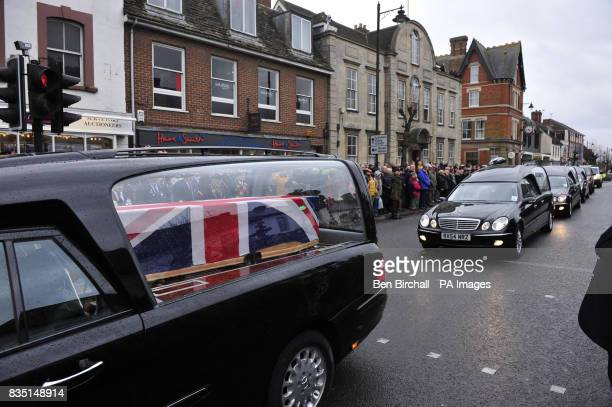 A Union Flag drapes a coffin in a hearse as it makes its way through Wootton Bassett as three soldiers from 1st Battalion The Rifles are repatriated...