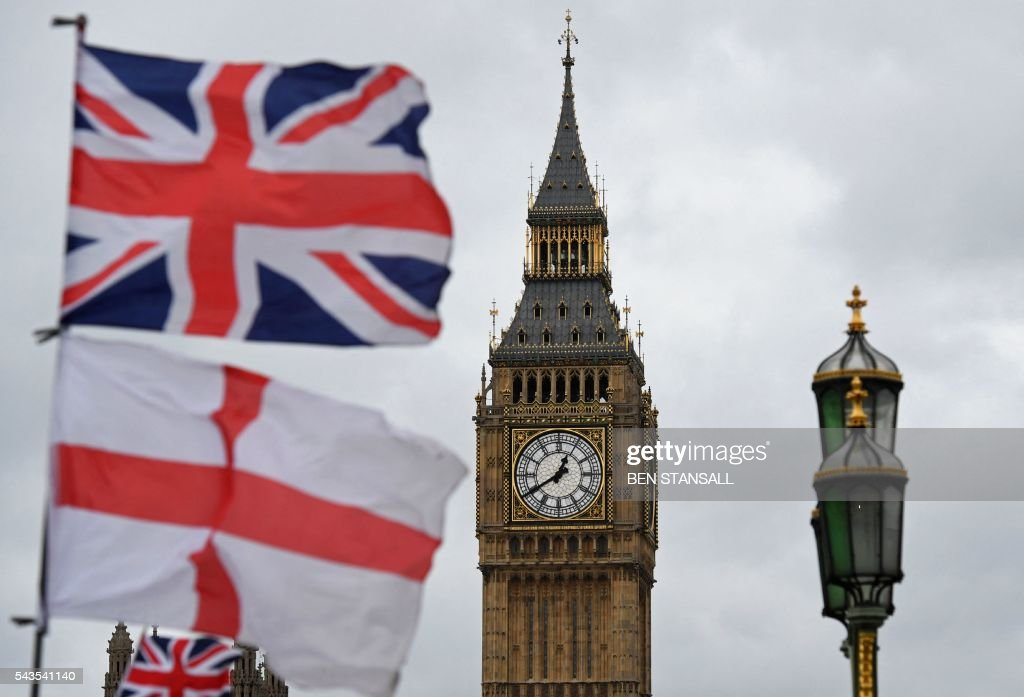 A Union flag flies above an English St. Georges Cross flag near the Big Ben clock face and the Elizabeth Tower at Houses of Parliament in central London on June 29, 2016. Europe's leaders meet Wednesday without Britain for the first time following its shock decision to leave the EU, trying to pick up the pieces and prevent further disintegration. Britain has been pitched into uncertainty by the result of the June 23 referendum, with Cameron announcing his resignation, the economy facing a string of shocks and Scotland making a fresh threat to break away. / AFP / BEN