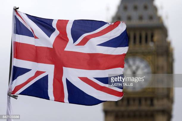 A Union flag flies in the wind in front of the Big Ben clock face and the Elizabeth Tower at the Houses of Parliament in central London on June 22...