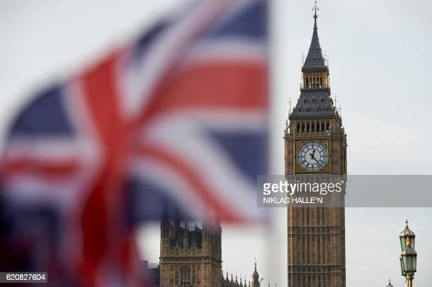 A Union flag flies in the wind in front of the Big Ben clock face and the Elizabeth Tower at the Houses of Parliament in central London on November 3...