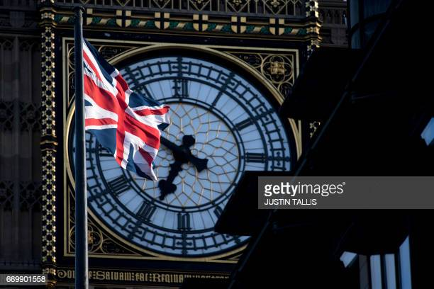 A Union flag flies in the wind in front of the clock face of Elizabeth Tower commonly referred to as Big Ben near the Houses of Parliament in...