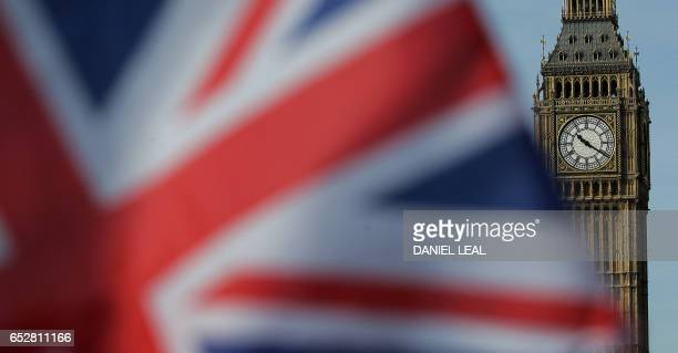 A Union flag flies near the Houses of Parliament comprising the House of Commons and the House of Lords in London on March 13 2017 British Prime...