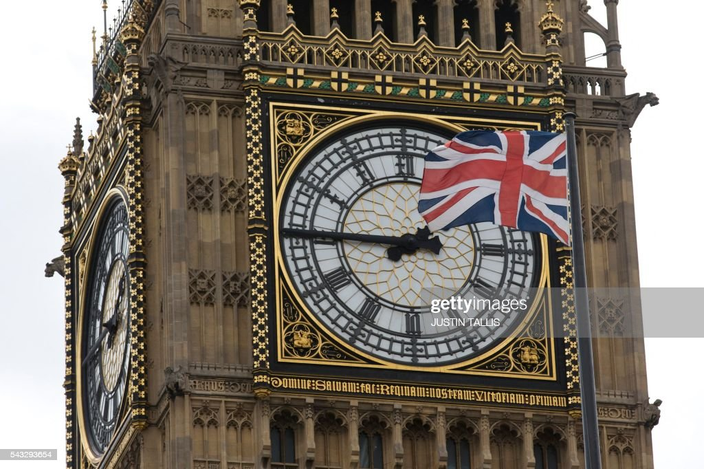 A Union flag is seen flapping in the wind in front of one of the faces of the Great Clock atop the landmark Elizabeth Tower that houses Big Ben at the Houses of Parliament in London on June 27, 2016. Top Brexit campaigner Boris Johnson sought Monday to build bridges with Europe and with defeated Britons who voted to remain in the EU in last week's historic referendum. London stocks sank more than 0.8 percent in opening deals on Monday, despite attempts by finance minister George Osborne to calm jitters after last week's shock Brexit vote. / AFP / JUSTIN