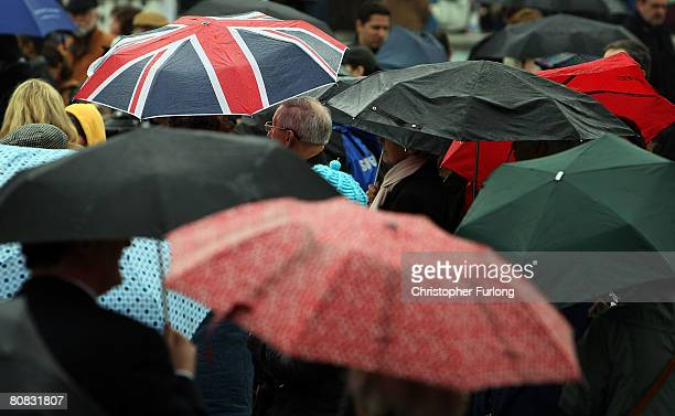 Union flag umbrella protects people watching a theatre company during the festivities celebrating Saint Georges's Day in Trafalgar Square April 23...