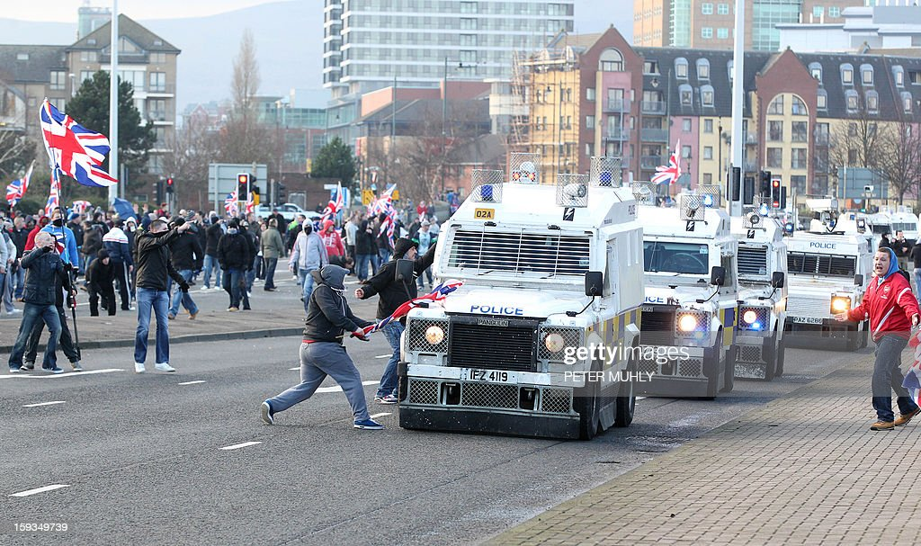 Union Flag waving loyalist protesters clash with police in riot gear and armoured vehicles in east Belfast, Northern Ireland on January 12, 2013 after the latest loyalist march against the decision to limit the days on which the Union Flag would be flown over Belfast City Hall. Northern Irish demonstrators loyal to Britain clashed with nationalists and police on Saturday in fresh protests against curbs on flying the British flag, leaving four officers injured, police said. The clashes were the latest to blight the British province after more than five weeks of violent disorder over the flag issue. AFP PHOTO / PETER MUHLY