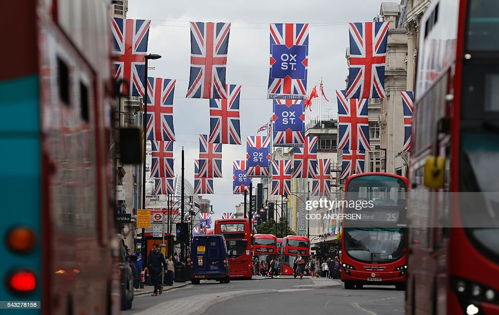 Union flags are attached between buildings along Oxford street in central london on June 27, 2016. Shares in banks, airlines and property companies plunged on the London stock exchange Monday as investors singled out the three sectors as being the most vulnerable to Britain's decision to leave the EU. / AFP / ODD