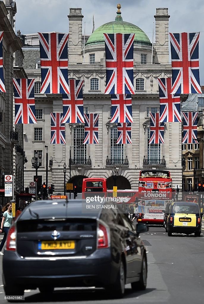 Union flags fly as banners across a street in central London on June 28, 2016. EU leaders attempted to rescue the European project and Prime Minister David Cameron sought to calm fears over Britain's vote to leave the bloc as ratings agencies downgraded the country. Britain has been pitched into uncertainty by the June 23 referendum result, with Cameron announcing his resignation, the economy facing a string of shocks and Scotland making a fresh threat to break away. / AFP / BEN