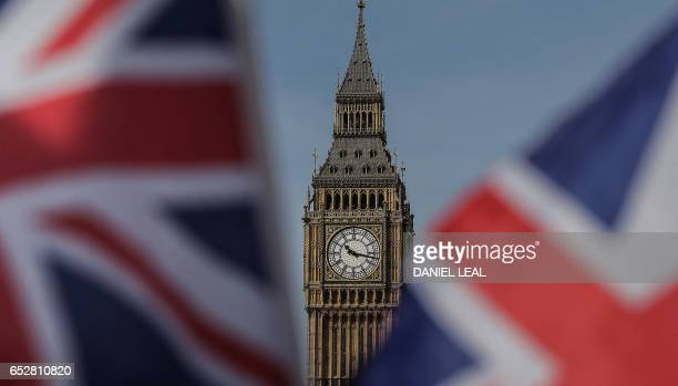 Union flags fly near the Houses of Parliament comprising the House of Commons and the House of Lords in London on March 13 2017 British Prime...
