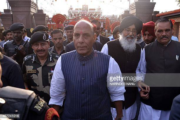 Union Home Minister Rajnath Singh Punjab state chief minister Parkash Singh Badal and Border Security Force Director General DK Pathak walk during...