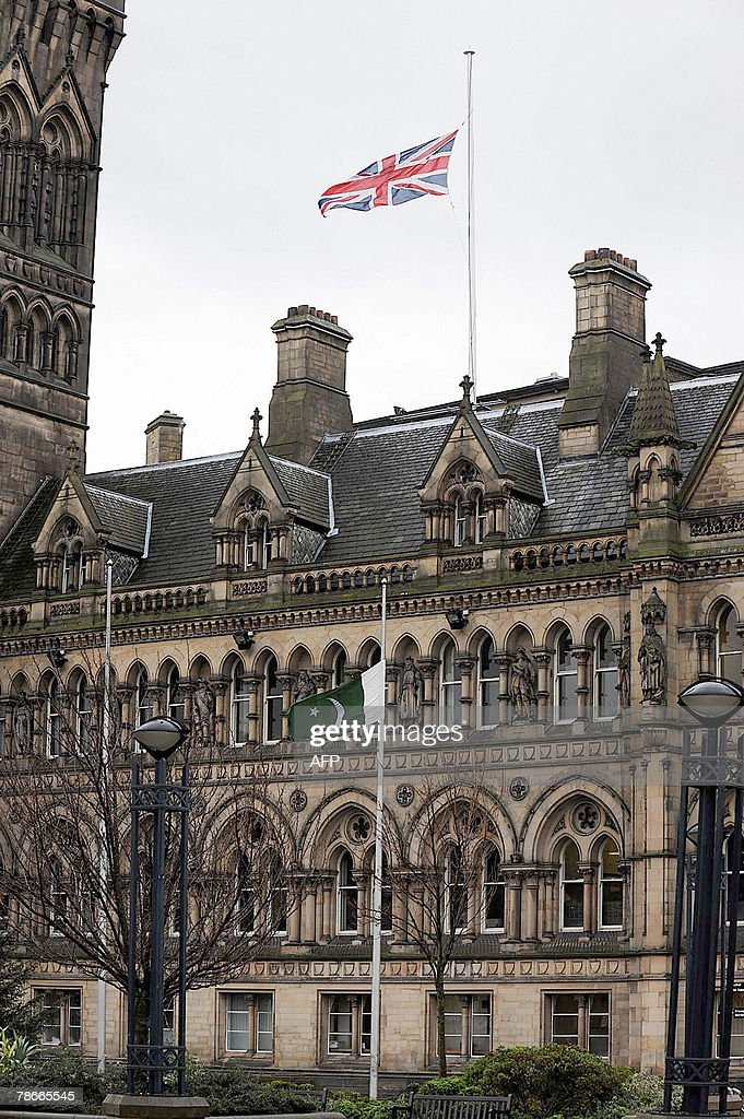 Union Jack and Pakistanese flags fly at half mast 28 December 2007 at Bradford Town City Hall. Britain strengthened its advice to travellers to Pakistan today, warning against 'all but essential travel' following the death of Benazir Bhutto. The Foreign Office said it was also advising travellers already in Pakistan to stay indoors 'until the situation becomes clearer'. The assassination of Pakistan opposition leader Benazir Bhutto sent shockwaves around the world on Friday with global leaders condemning the act as markets reacted with fear to the new blow to international stability. AFP PHOTO/TONY SPENCER