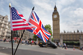 Union Jack flag and the Stars and Stripes flag of the USA, fluttering together in front of Big Ben in Westminster, London
