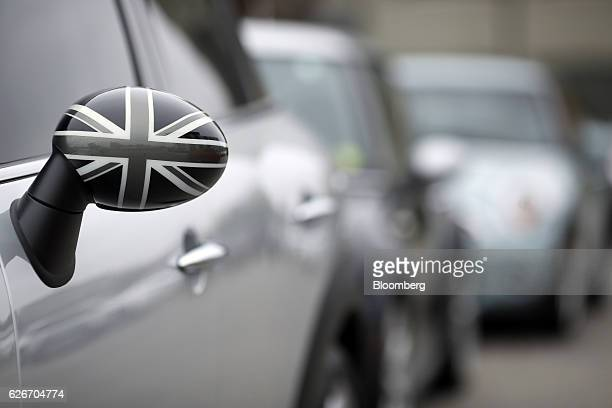 A Union Jack flag is displayed on the side view mirror of a Bayerische Motoren Werke AG MINI vehicle at a car dealership in Louisville Kentucky US on...