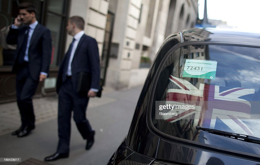 A Union Jack pillow sits on the parcel shelf of a London taxi cab as businessmen walk past in London, U.K., on Friday, Aug. 17, 2012. Banks, insurers and other financial-services firms may eliminate a total of about 3,000 jobs across greater London as companies in the New York region add 9,000, according to U.K.-based researcher Oxford Economics Ltd. Photographer: Simon Dawson/Bloomberg via Getty Images