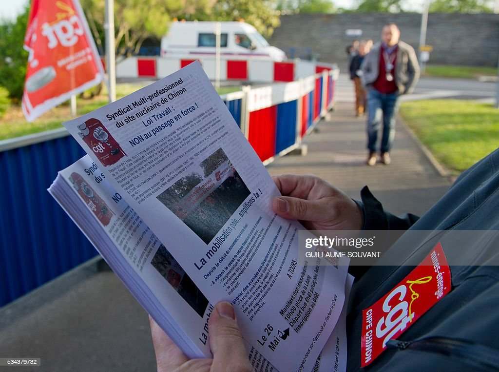 A union member distributes leaflets at the entrance of the Chinon nuclear power station during a strike to protest against the government's proposed labour reforms on May 26, 2016 in Avoine, central France. France faced fresh strikes after nuclear power station workers voted to join gathering protests against labour law reforms that have forced the country to dip into strategic fuel reserves due to refinery blockades. / AFP / GUILLAUME