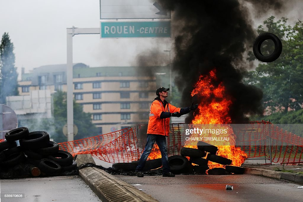 A union member throws a tyre onto a pile of tyres set ablaze at a blockade onto a main road leading to downtown Rouen, northwestern France, on May 31, 2016 to protest against the government's planned labour law reforms. / AFP / CHARLY