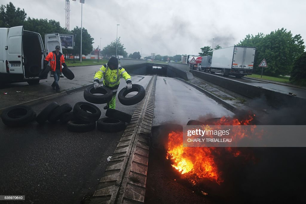 Union members throw tyres onto a pile of tyres set ablaze at a blockade onto a main road leading to downtown Rouen, northwestern France, on May 31, 2016 to protest against the government's planned labour law reforms. / AFP / CHARLY