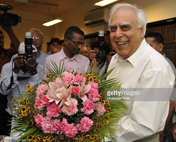 Union Minister for Communications and Information Technology Kapil Sibal is greeted with a bouquet as he takes additional charge of Law Ministry on...