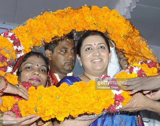 Union Minister Smriti Irani being felicitated by people after her arrival during a rally where she paid premiums for PM's Suraksha Bima Yojana for...